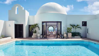 Large square pool in a sunny courtyard with a domed circular room beyond
