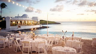 White circular tables on a beach at sunset, lit with fairy light