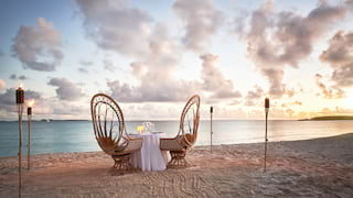 Two curved wooden chairs at a table on an Anguillan beach at sunset