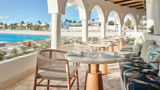 A row of circular tables on a curved restaurant terrace over the beach