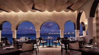 Restaurant with large arched windows overlooking the sea at night