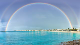 A rainbow in blue skies over the turquoise water of Maundays Bay
