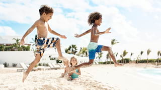 Three young kids jumping and playing on a beach