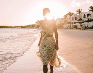 Mujer paseando por una costa arenosa al atardecer
