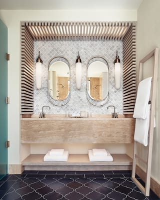 Two oval-shaped mirrors above twin bathroom sinks