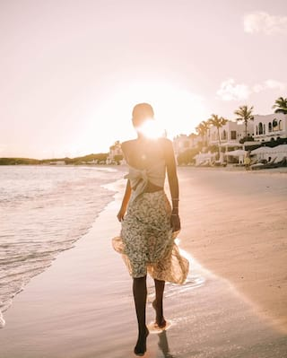 Lady in a sundress walking barefoot down a beach a sunset