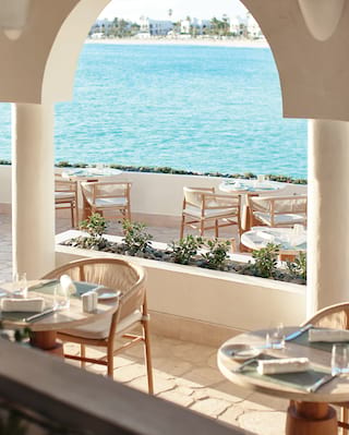 Circular tables dotted across a restaurant terrace overlooking the beach