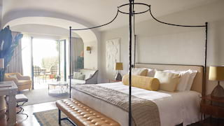Contemporary wrought-iron four-poster bed with assorted yellow cushions