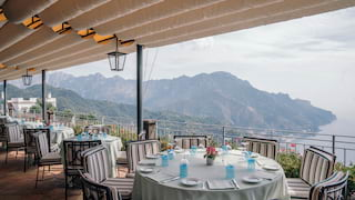 Large circular table surrounded by pinstripe chairs on a hilltop restaurant terrace