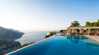Mirror-still infinity pool beside a stone-paved poolside overlooking the Amalfi Coast