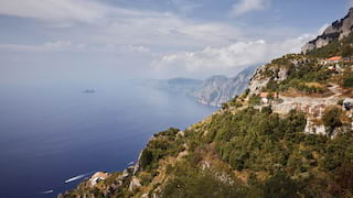 Italian village on a hilltop with views along a cliff-lined coast under blue skies