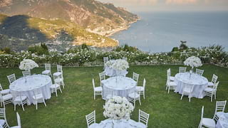 Manicured lawn overlooking the Amalfi Coast dotted with circular banquet tables