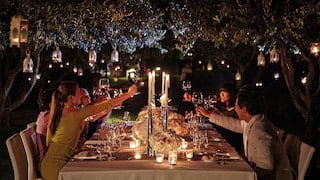 A group toasting across a candlelit table under two trees with hanging lanterns above