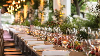 Rows of shimmering wine glasses on a long candlelit banquet table under a gazebo