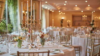 Circular banquet tables lit with candelabras and set for a wedding in an elegant room