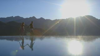 Couple walking along the edge of the infinity pool at Belmond Hotel Caruso