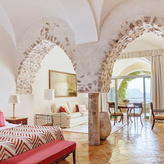Spacious, light and airy hotel suite with exposed stone arches and red accents