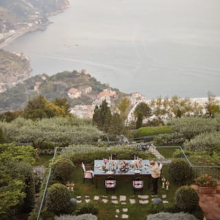 Outdoor table coated in flowers and candles overlooking lush hillside gardens