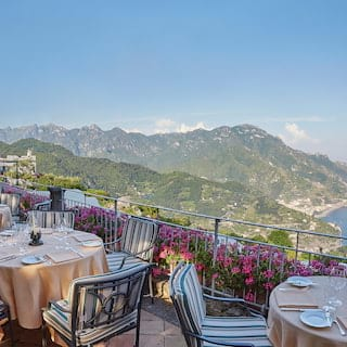 Restaurant terrace with round tables and pinstripe chairs overlooking the Amalfi Coast