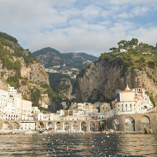 View from across the water of a coastal village nestled between tall cliffs