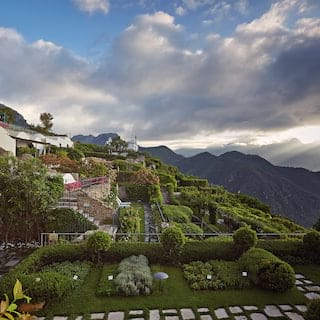 Neatly manicured Italian gardens dotted with stone paved paths beside a hilltop villa