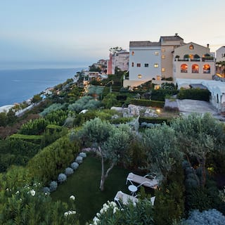 Lush Italian gardens surrounding a luxurious hilltop villa at sunset