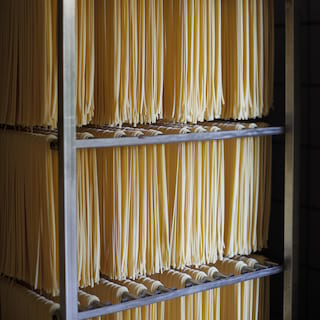Rows of spaghetti pasta stretching on racks piled three high