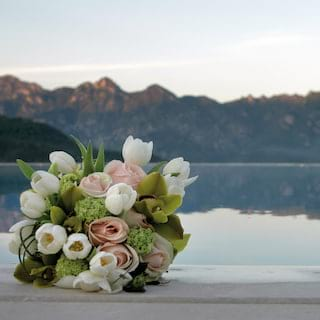 A bouquet of white tulips and pink roses on a poolside overlooking the hills of Amalfi