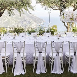 Long banquet table set for a wedding with grand floral centerpieces and coastal views