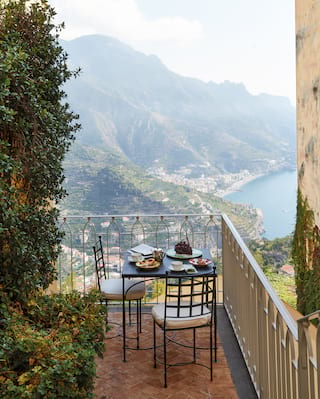 Breakfast table on a terracotta-tiled garden balcony overlooking the Amalfi Coast