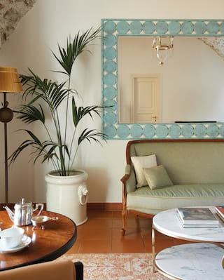 Sea green sofa and marble-topped coffee table in a terracotta-tiled lounge area