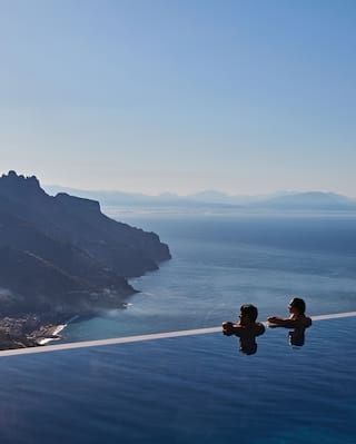 A couple looking over the edge of an outdoor infinity pool on the Amalfi Coast