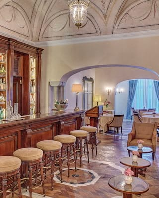 Double-height bar with a barrel vaulted ceiling, parquet floor and mahogany counter