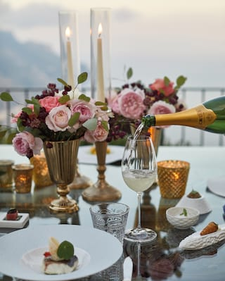 Champagne being poured into a glass on a table with pink flowers in gold vases