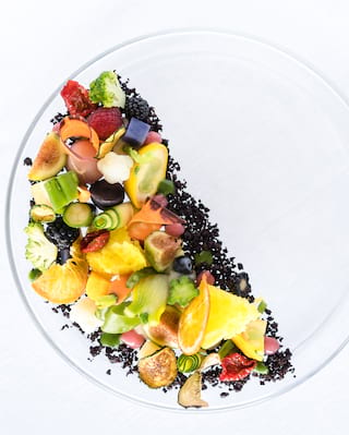 Birds-eye-view of a vibrant fruit salad dessert on a bed of poppy seeds