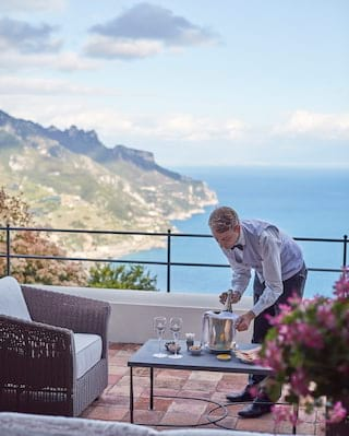 Waiter in a light grey waistcoat placing a bottle of chilled champagne on a balcony table
