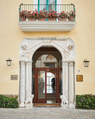 Stone-carved entrance to an Italian villa with Corinthian columns and cherub faces