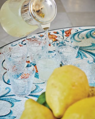 Jug of fresh lemonade being poured into crystal glasses on a vibrant ceramic plate