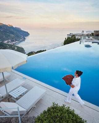 Pool attendant carrying red towels alongside a mirror-still infinity pool at sunset