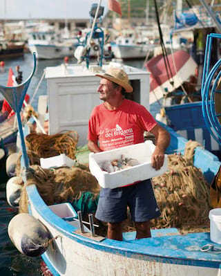 Man in a red T-shirt in a fishing boat holding a box of freshly caught fish