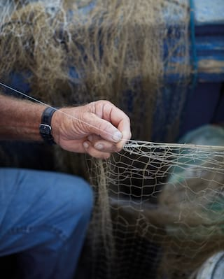 Close-up of a fisherman sewing a fishing net