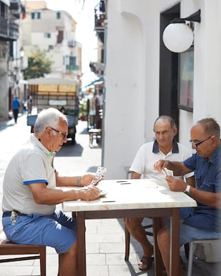Three middle-aged Italian men playing cards at an outdoor table in a village center