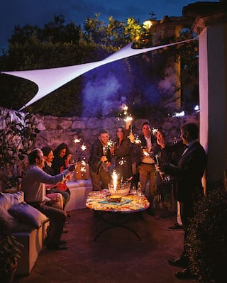 A smiling group of friends holding lit sparklers in a stone-walled garden seating area