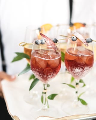 Close-up of four red wine sangria cocktails in wine glasses garnished with blueberries