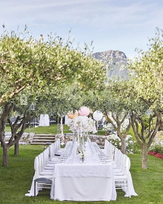 Long banquet table set for a wedding in an orchard lined with flower beds