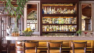 Three yellow leather bar stools at a marble bar top, with liquor on shelves behind