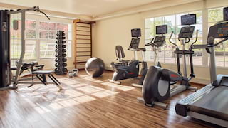 Gym studio with various gym equipment and polished hardwood floor