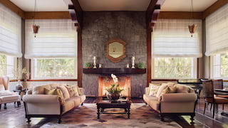 Two pale cream sofas and a coffee table before a fireplace on a stone wall