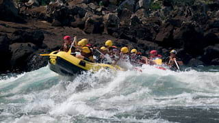 A yellow inflatable raft with passengers paddling against white water rapids