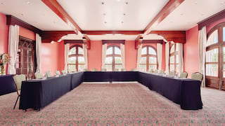 Large pink room with conference tables in a U-formation